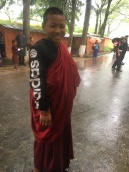 A young Buddhist monk accessoring his robes--American style