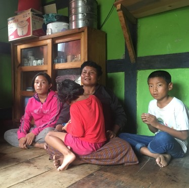 most families sit on the floor. Notice the Momo steamer on the cabinet behind them.