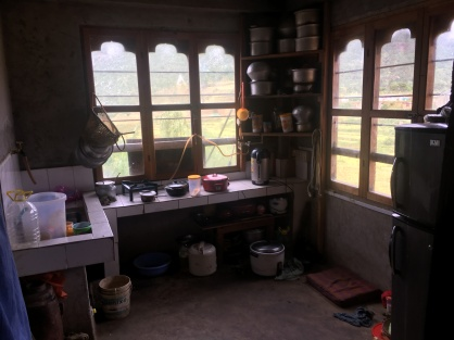 this is a very modern kitchen for Bhutan. This family has a refrigerator and recently updated for indoor water.