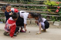 school kids playing jax or marble (?) using stones